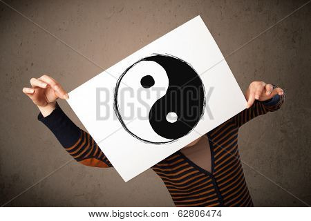 Young woman holding a paper with a yin-yang symbol on it in front of her head