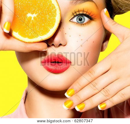 Beauty Model Girl takes Juicy Oranges. Beautiful Joyful teen girl with freckles, funny hairstyle, yellow makeup and manicure. Professional make up. Orange  Slices