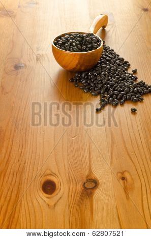 Frijoles, mexican black beans, on wooden background, biologic culture