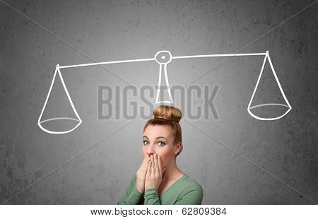 Pretty young lady taking a decision with scale above her head