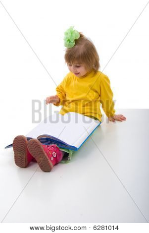 Cute Little Schoolgirl Sitting With A Books