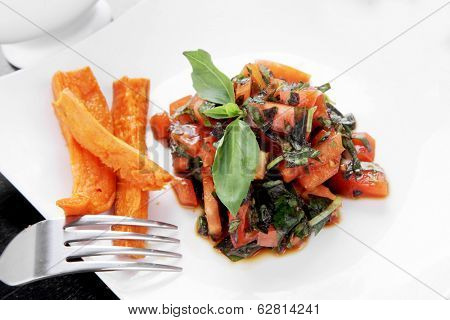 vegetable salad : cherry tomatoes and basil with sweet baked potato served on white plate with sauce boat full balks soy sauce on wood