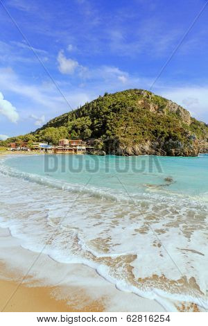 Paleokastritsa beach on Corfu, Greece, with a restaurant taverna at the end of it.