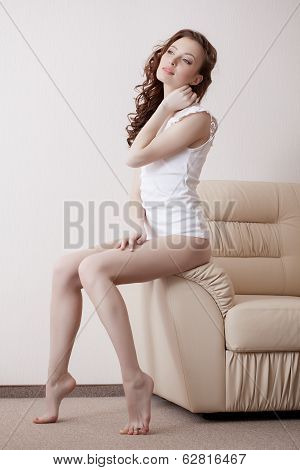Dreamy leggy model posing on leather couch