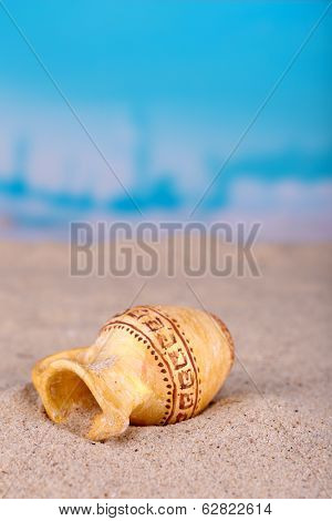 Greek ceramic amphora on sand, close up