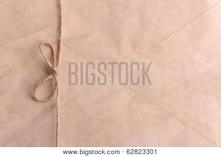 String tied in  bow on beige paper packaging close-up