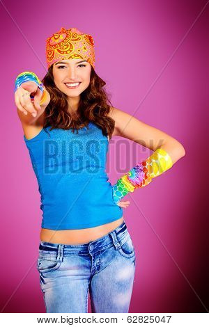 Cheerful teenager girl in bright casual clothes smiling at the camera.