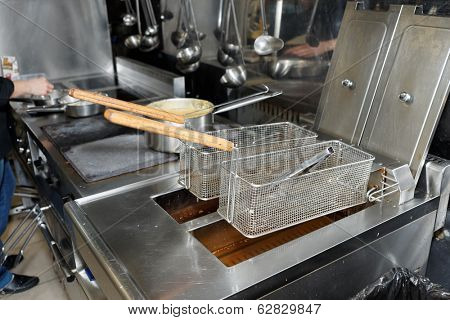 Deep fryers with boiling oil on fast food kitchen