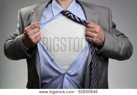 Businessman in classic superman pose tearing his shirt open to reveal t shirt with blank chest for message