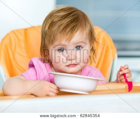 baby  girl in a highchair for feeding with a spoon and a plate in the kitchen at home