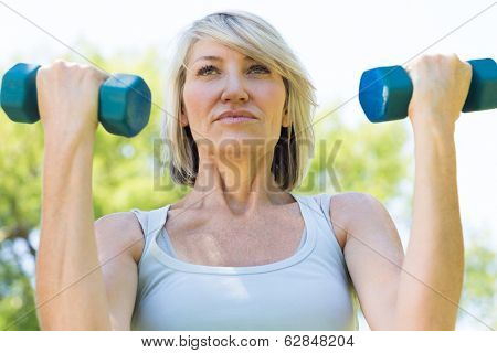 Closeup of sporty woman lifting dumbbells in the park