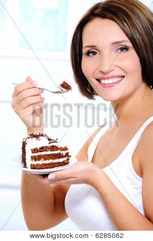 Girl With Cake On Plate Brings  Spoon To A Mouth