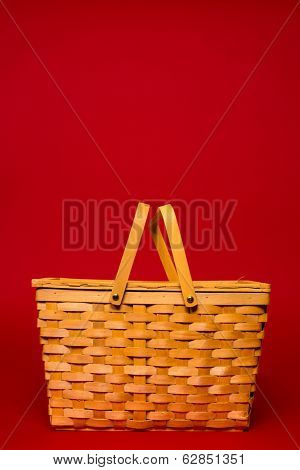 A brown wicker basket on a red background with copy space