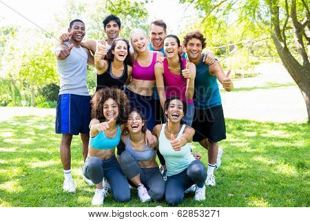 Group of friends in sportswear showing thumbs up at the park