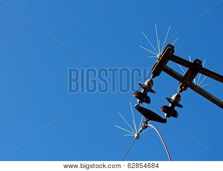 High-voltage Electrical Insulator Of Electric Line Against Blue Sky