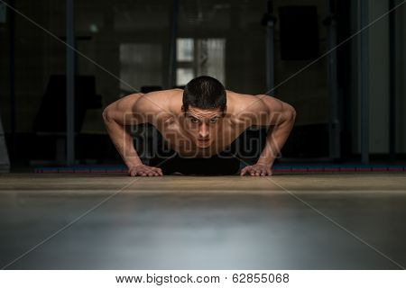 Young Man Doing Press Ups In Gym