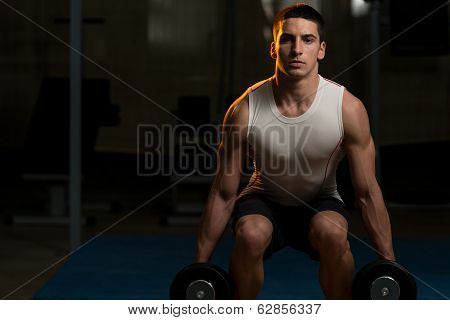 Young Men Doing Squats With Dumbbell In Gym