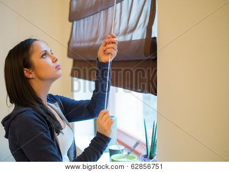 Young woman opening jalousie in her apartment