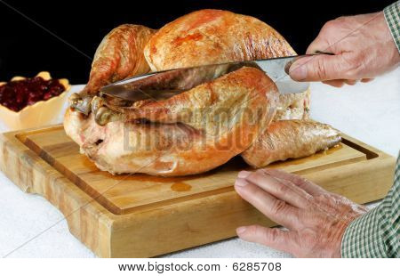 Roast Turkey On Cutting Board With Hands And Knife Carving.