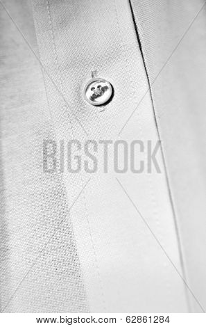 Detail of white dress shirt button and cotton texture