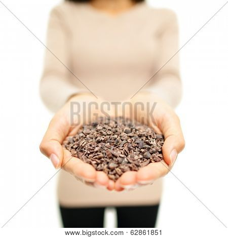 Cacao nibs from cocoa beans. Superfood - woman showing handful heap of raw cacao nibs as part of healthy eating lifestyle.
