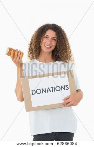 Happy volunteer holding a box of donations and jam jar on white background