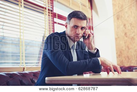 Pensive businessman sitting and talking on the phone at office