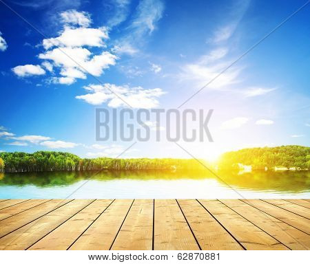 Sunset on forest lake and wooden board background