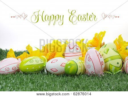 Happy Easter Colorful Pink And Green Easter Eggs With Yellow Daffodils On Green Grass Against White