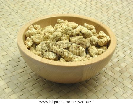 Wooden Bowl With Soy Granules On Rattan Underlay