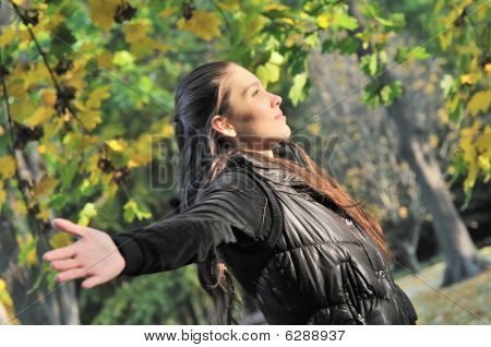 Woman Enjoys Sun In Autumn Time Outdoors