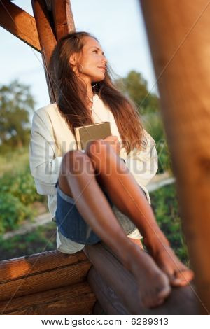 Young Lady With Book In Summerhouse On Sunset