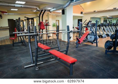 different gym machines and  equipment in gym interior