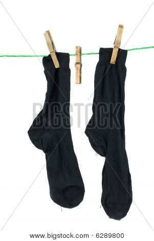 Two Black Socks Hanging On Rope