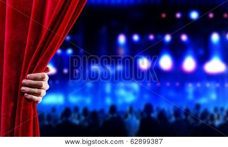 Hand of businessman opening red velvet curtain