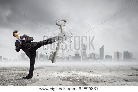 Angry businessman crashing stone key with kick