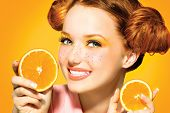 stock photo of freckle face  - Beauty Model Girl takes Juicy Oranges - JPG