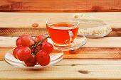grapes with tea and cake on wooden table