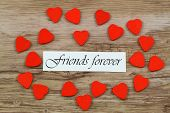 stock photo of  friends forever  - Friends forever card with little wooden hearts on wooden surface - JPG