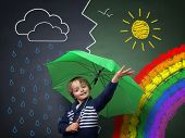 stock photo of end rainbow  - Child holding an umbrella standing in front of a chalk drawing of changing weather from rain storm to sun shine with a rainbow on a school blackboard - JPG