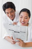 Couple in bathrobes reading newspaper together in the morning at home in the living room