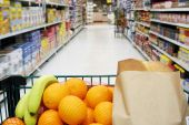 picture of grocery cart  - Grocery cart loaded with fresh fruit and bread moving through the aisle - JPG