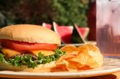 stock photo of potato chips  - Perfect cheeseburger outside in summer with lemonade and watermelon - JPG