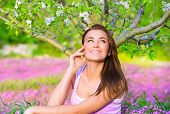 Happy woman in blooming garden, having fun outdoors, sitting down on pink floral meadow, spring time