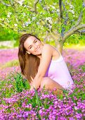 Cheerful smiling female spending time on backyard, enjoying apple tree blossom, sitting on pink flor