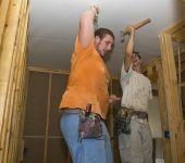 Two Men Putting Up Sheetrock