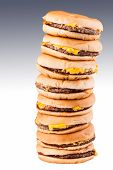 stock photo of morbid  - a very tall pile of cheesburgers representing gluttony or a very special fast food offer - JPG