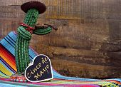 stock photo of mexican fiesta  - Happy Cinco de Mayo 5th May party celebration with with fun Mexican cactus and blackboard sign with text against a dark retro wood background - JPG