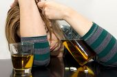pic of bing  - Drunk woman with bottle in her hand and pills on the table - JPG