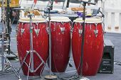 foto of congas  - Trio of Red Conga Drums on Live Concert Stage